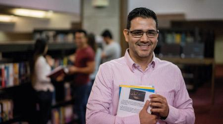 Foto de una persona en la biblioteca con un libro en sus manos
