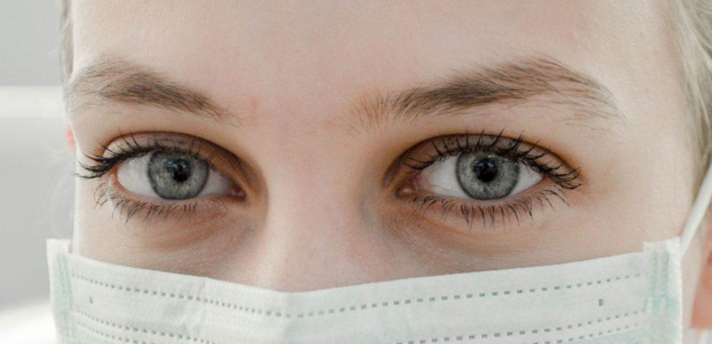Foto de rostro de mujer con ojos azules y tapabocas