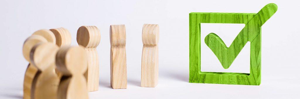 Fichas en madera en forma de cuerpo humano con una ficha final que representa un chulo