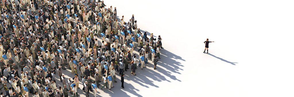 Multitud de personas que caminan hacia un lugar liderado por una mujer