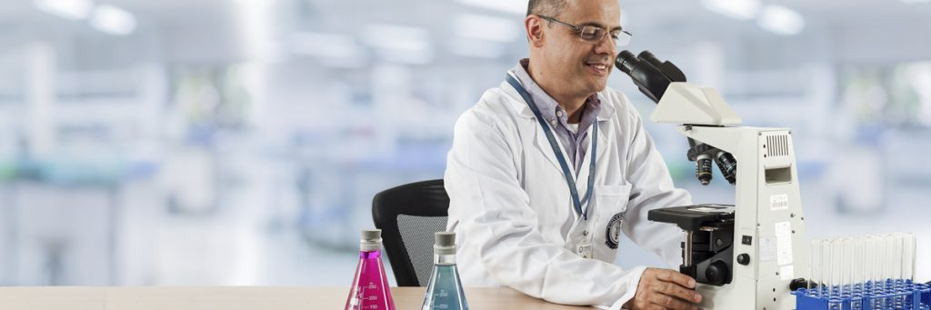 médico en laboratorio observando a través de un microscopio.
