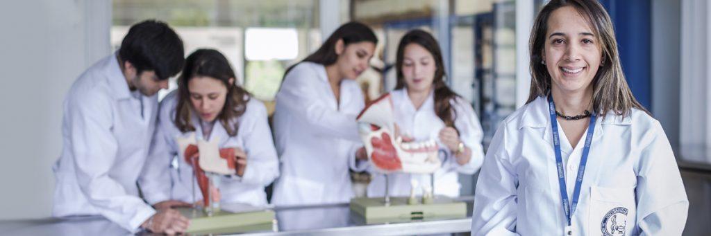 Profesora y estudiantes con maniquíes de odontología.