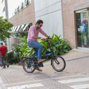 Foto de estudiante ingresando a la Universidad en una bicicleta eléctrica