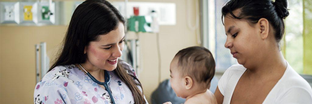 Foto de residente pediatra de la Universidad CES atendiendo a un niño, acompañado de su madre