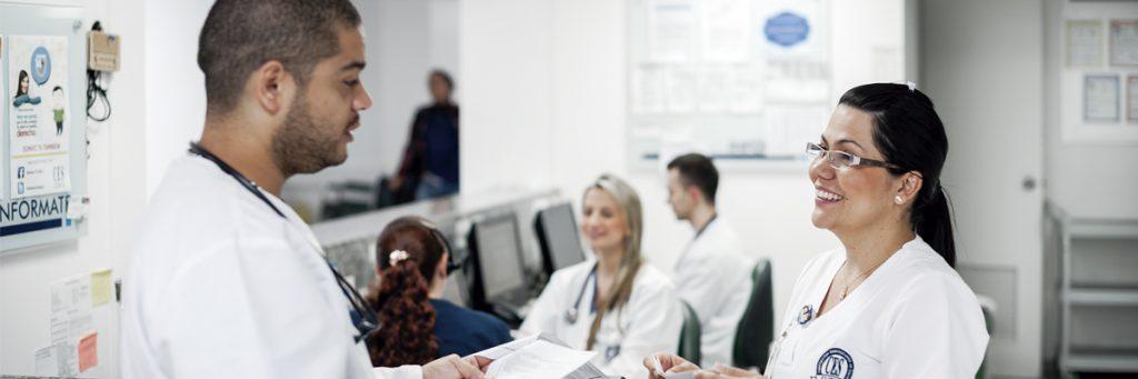 Foto de residente acompañado de enfermera, entregando historia clínica en la sala de urgencias.