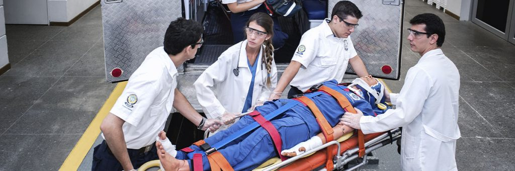 Photo students performing prehopital care process with ambulance and patient simulator.