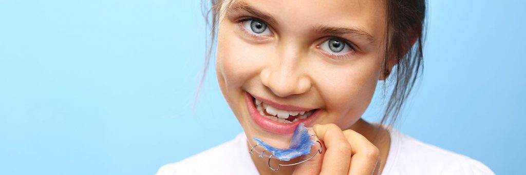 photograph of girl with her retainer to correct her teeth