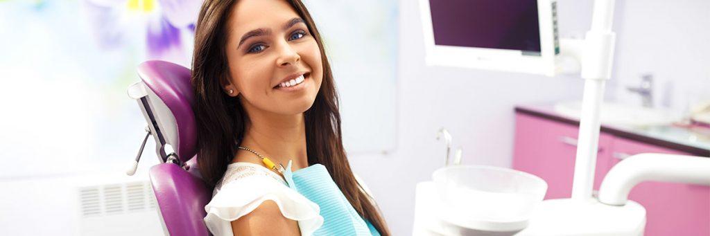 Fotografía de paciente sonriendo en la silla de odontología mientras espera para ser atendida