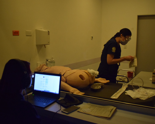 Photograph of a student in a CEC office performing a practice procedure
