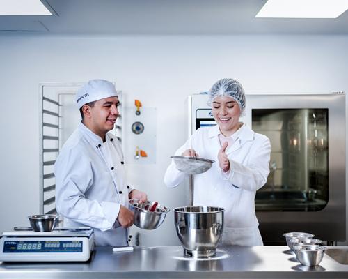 Docente y estudiante realizando ejercicios de gastronomía en el laboratorio de alimentos y gastronomía