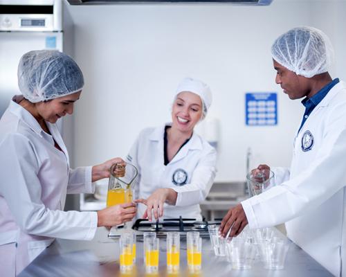 Docente y estudiante preparando pruebas para el laboratorio de evaluación sensorial