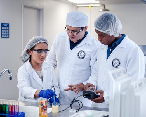 docente y estudiantes realizando análisis de alimetnos en el laboratorio de alimentos y gastronomía