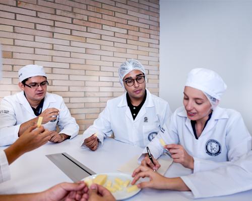 docente y estudiantes realizando prueba de alimentos en el laboratorio de evaluación sensorial
