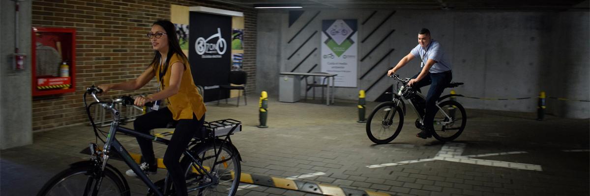 Fotografía de dos empleados de la Universidad utilizando las bicicletas