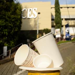 Vasos plásticos con el fondo de la Universidad CES al fondo