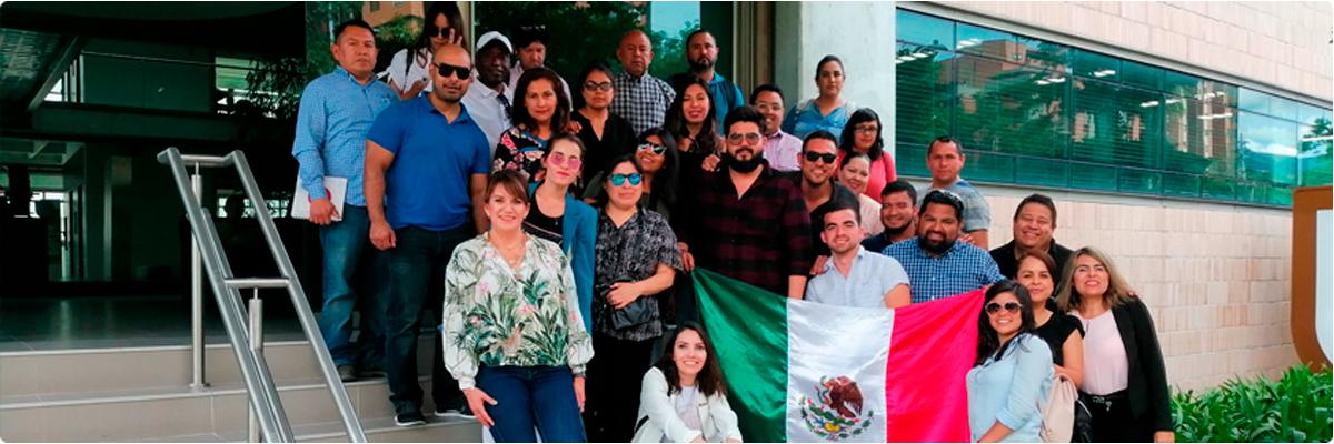 Grupo de mexicanos mostrando la bandera de su país