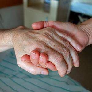 Fotografía de la mano de un anciano sostenida por la mano de un familiar