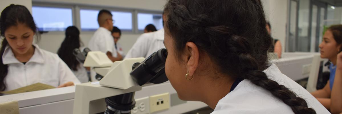 Fotografía de estudiante mirando por un microscópio
