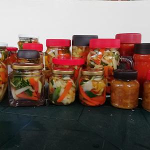 Fotografía de tarros de vidrio que contienen conservas de legumbres, mermeladas, entre otros.