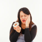 image of woman with pain in the mouth when biting a sweet