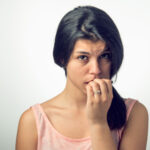 picture of woman biting her nails
