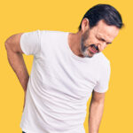 photograph man complaining of back pain