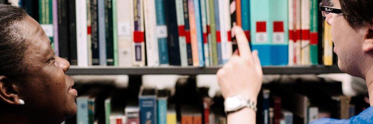 fotografía de dos personas buscando un libro en una estantería