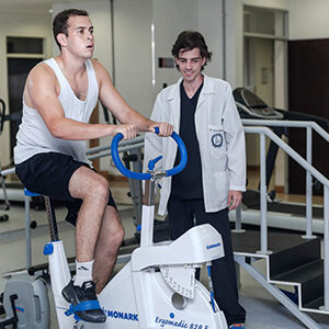 fisioterapeuta acompañando asitiendo a un paciente en bicicleta estática