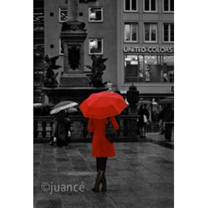 fotografía de una mujer de rojo con una sombrilla resaltando entre el público