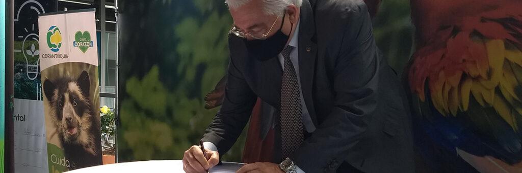 foto del rector de la universidad ces firmando unos documentos