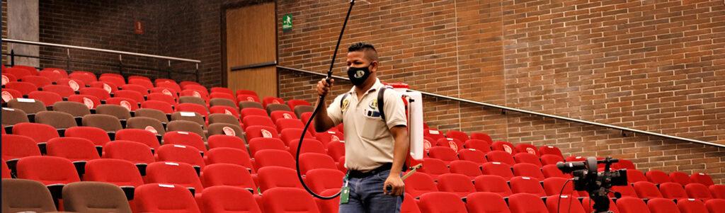 hombre desinfectando el teatro de la Universidad CES