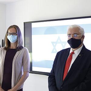 fotografia de dos personas parada con la bandera de Israel en la parte de atras de ellos