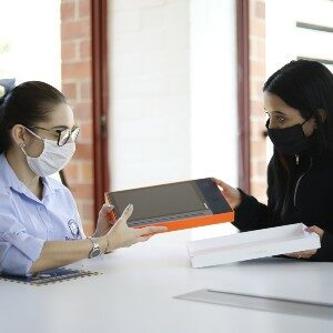 image of a woman handing over a digital tablet to another