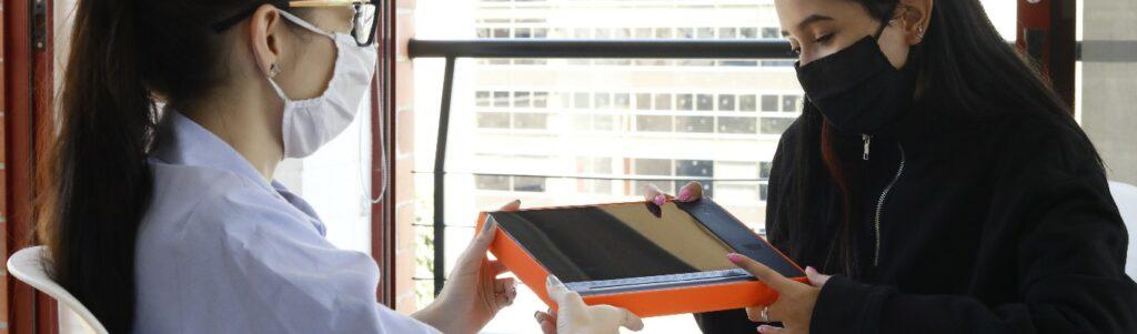 imagen de una mujer entregándole a otra una tableta digital