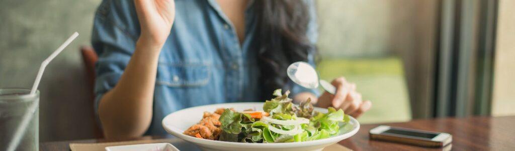 imagen de un plato de verduras con una mujer en la parte de a tras comiendo del plato
