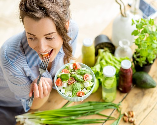 image where a young woman is eating a plate of vegetables
