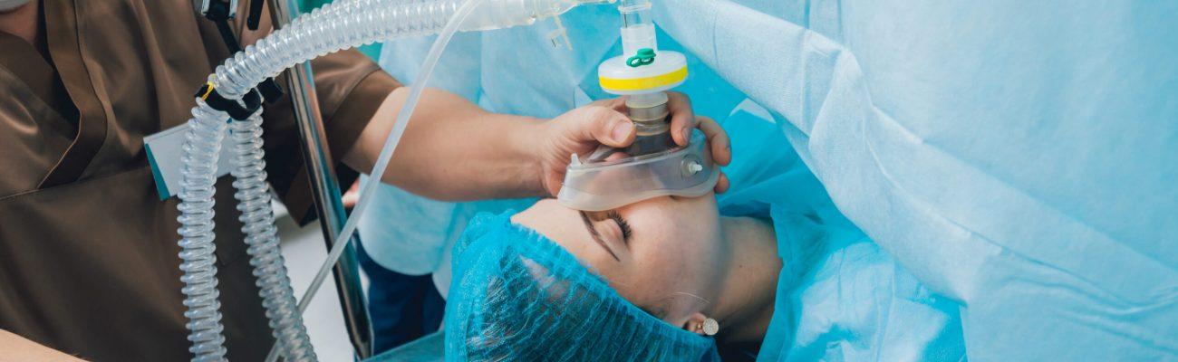 imagen de una mujer siendo dormida con anestesia por personal medico